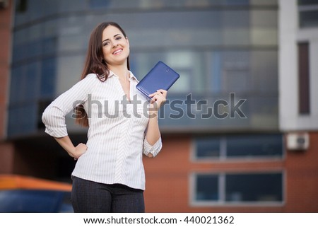 Portrait of pretty student or businesswoman in smart casual using digital tablet outdoors