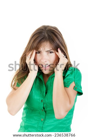 Portrait of pretty student woman with huge headache with both hands on her head looking in camera with painful face expression - stock photo