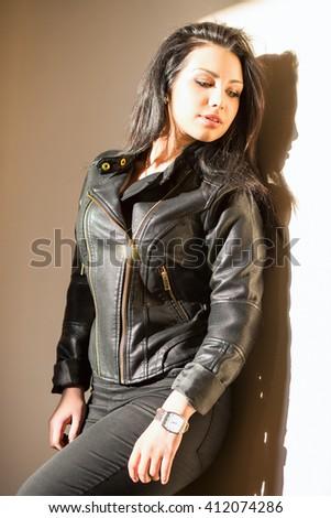 Portrait of pretty thoughtful woman posing near the wall - stock photo
