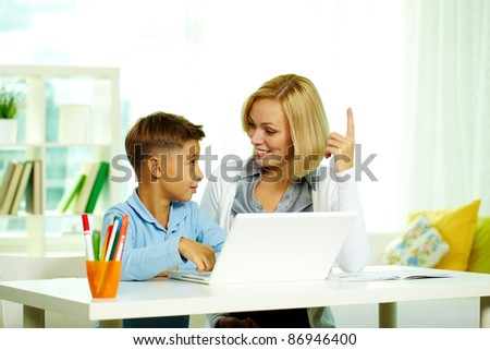 Portrait of pretty tutor and diligent pupil discussing ideas while working with laptop - stock photo