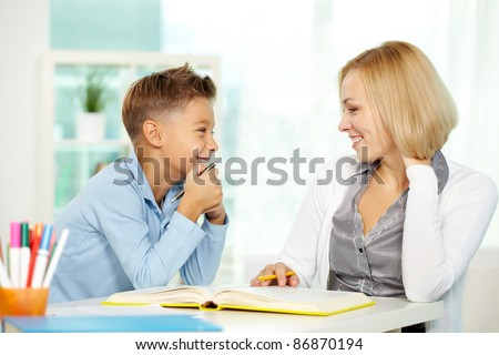Portrait of pretty tutor and diligent pupil looking at each other while communicating - stock photo