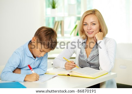 Portrait of pretty tutor looking at camera with diligent pupil making notes near by - stock photo