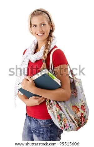 Portrait of pretty university student girl in trendy clothes with book handheld, smiling at camera.? - stock photo