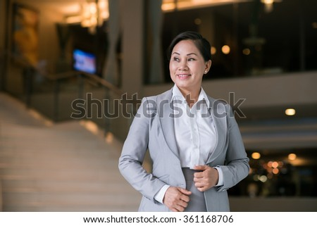 Portrait of pretty Vietnamese business lady smiling and looking sideways - stock photo