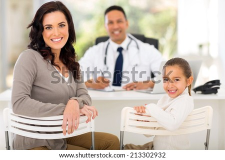portrait of pretty woman and her daughter in doctor's office for check up - stock photo