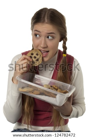 Portrait of pretty woman eating chocolate cookie against white background - stock photo