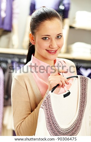 Portrait of pretty woman holding cardigan and looking at camera in clothing department