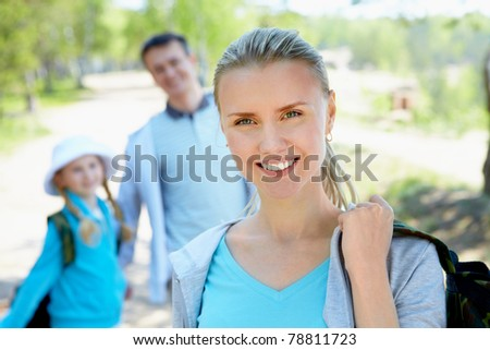 Portrait of pretty woman looking at camera with her family on background in summer - stock photo