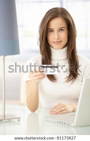 Portrait of pretty woman online shopping, using laptop computer and credit card.? - stock photo