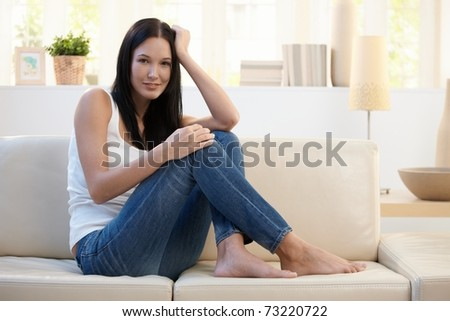 Portrait of pretty woman posing on couch at home, smiling at camera.?