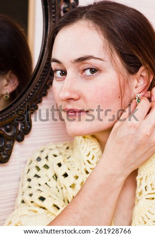 Portrait of pretty woman tries earrings at mirror - stock photo
