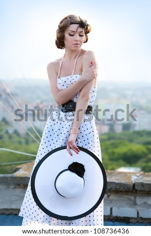 Portrait of pretty woman wearing white dress and straw hat in sunny warm weather day.  The girl with the hat in her hands. - stock photo
