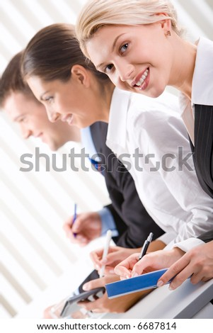 Portrait of pretty woman with friendly smile on the background of business people