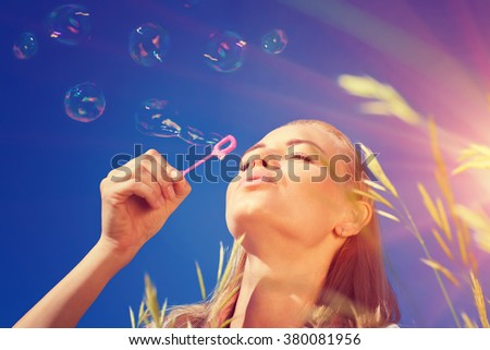 Portrait of pretty woman with pleasure blowing soap bubbles over blue sky background, having fun outdoors in sunny day - stock photo