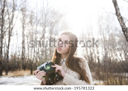 Portrait of pretty young adult girl taking photographs with old vintage retro camera on winter tree and snow background Cute slim woman looking on camera against sun rays and sunset sky background - stock photo
