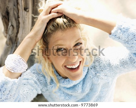 Portrait of pretty young blond woman sitting on beach in Maui, Hawaii smiling and holding back hair with hands.
