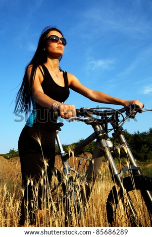 Portrait of pretty young brown haired woman riding a bike with text space - stock photo