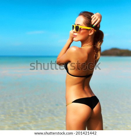 Portrait of pretty young brunette sexy sport woman in black bikini standing on the beach on tropic island and having fun on vacation  - stock photo