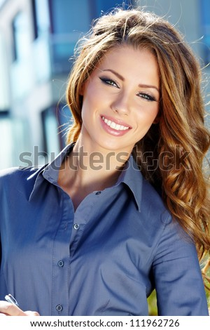 Portrait of pretty young business woman smiling - stock photo