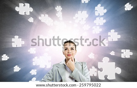 Portrait of pretty young businesswoman and many puzzle elements around - stock photo