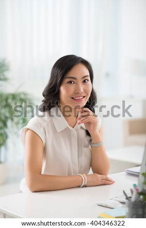 Portrait of pretty young Chinese woman sitting at her workplace