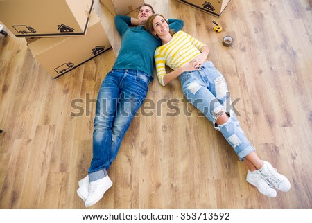 Portrait of pretty young couple moving in new home. - stock photo