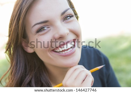 Portrait of Pretty Young Female Student with Pencil on Campus Lawn. - stock photo