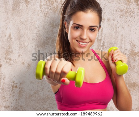 portrait of pretty young girl exercising with weights - stock photo
