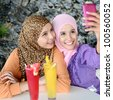 Portrait of pretty young Muslim woman smile for  camera phone capture - stock photo