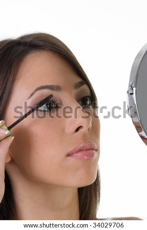 Portrait of pretty young woman applying mascara - stock photo
