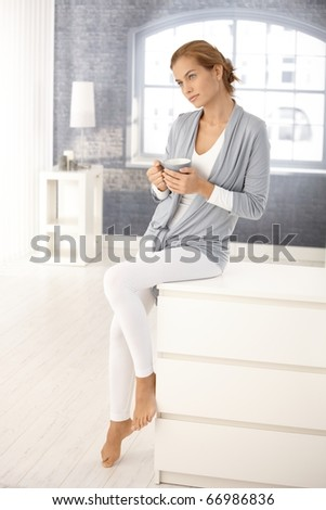 Portrait of pretty young woman at home, sitting in bright living room, daydreaming with tea mug in hands.? - stock photo