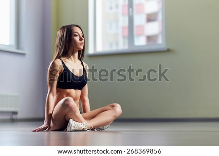 Portrait of pretty young woman doing yoga exercise in gym. The young girl meditates in a gym. Portrait of fitness sporty girl doing yoga exercise in gym. Young woman practicing yoga indoors. - stock photo
