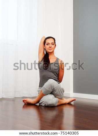 portrait of pretty young woman doing yoga exercise on floor - stock photo