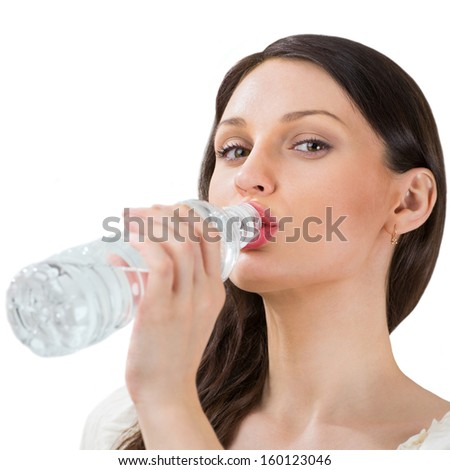 Portrait of pretty young woman drinking water from plastic bottle - stock photo