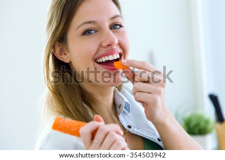 Portrait of pretty young woman eating carrot in the kitchen. - stock photo