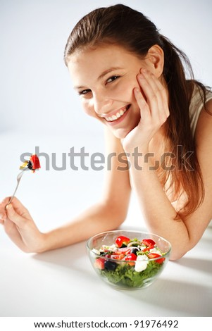Portrait of pretty young woman eating vegetable salad - stock photo