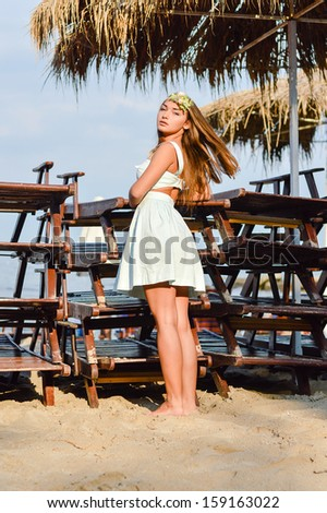Portrait of pretty young woman enjoying sunny day on the sea beach on summer outdoors background
