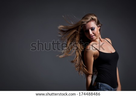 Portrait of pretty young woman flinging long  hair into air.