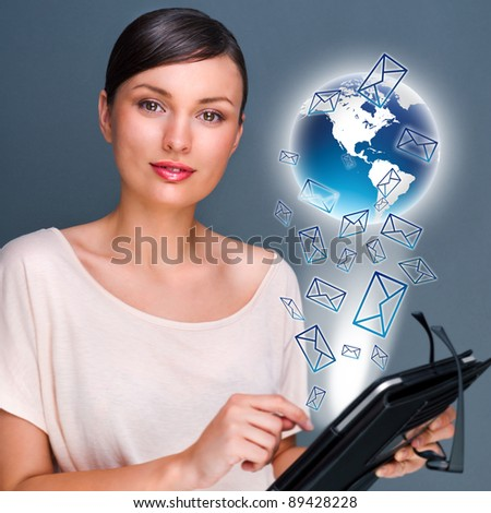 Portrait of pretty young woman holding Touch Screen tablet computer and working with her mail - stock photo