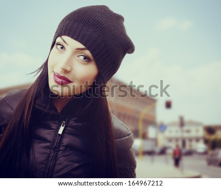 portrait of pretty young woman in black hat and jacket over urban background, toned - stock photo