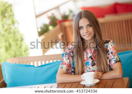 portrait of pretty young woman sitting in cafe with  cup of tea or coffee