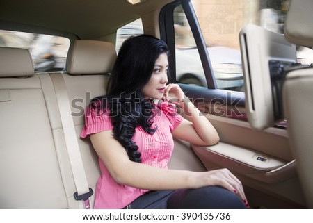 Portrait of pretty young woman sitting in the seat back of luxury car and look at the window - stock photo