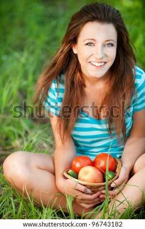 Portrait of pretty young woman sitting on green grass holding a basket with fruit and vegetables at summer green park - stock photo
