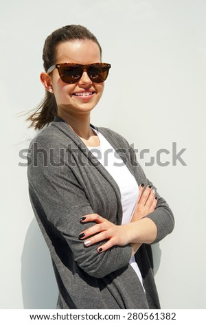 portrait of pretty young woman smiling closeup with crossed arms - stock photo