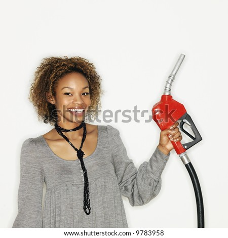 Portrait of pretty young woman smiling holding gas pump nozzle on white background. - stock photo