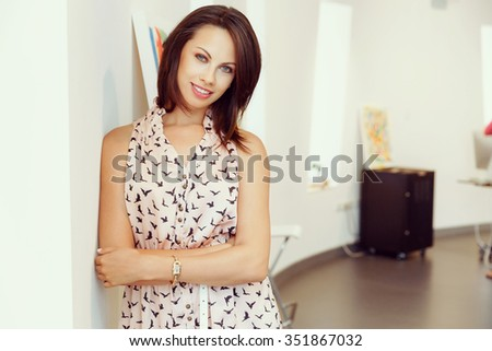 Portrait of pretty young woman standing in gallery