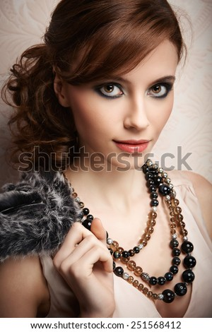 Portrait of pretty young woman with beads and furs - stock photo