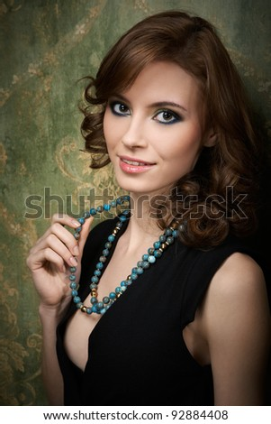 Portrait of pretty young woman with blue beads - stock photo