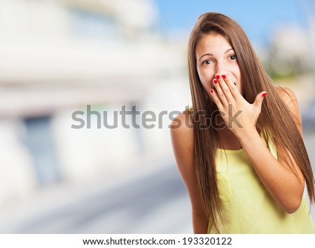 portrait of pretty young woman with her hand covering her mouth - stock photo