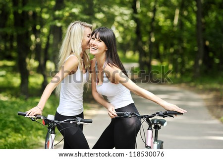 Portrait of pretty young women with bicycle in a park smiling - outdoor - stock photo